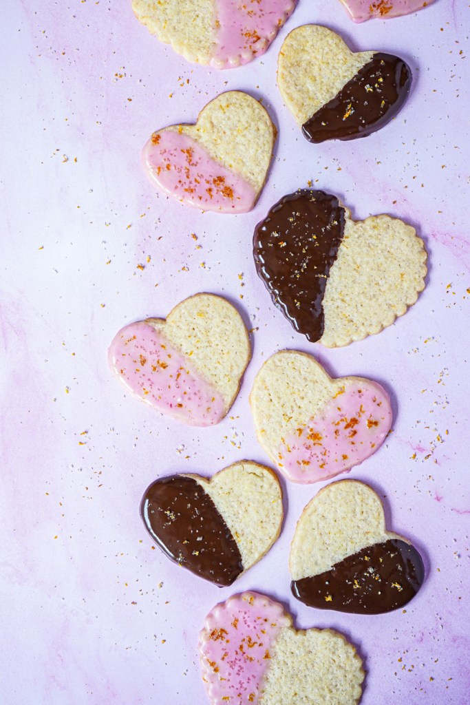 Aerial view of Blood Orange Shortbread Cookies cut into hearts and arranged in a line.