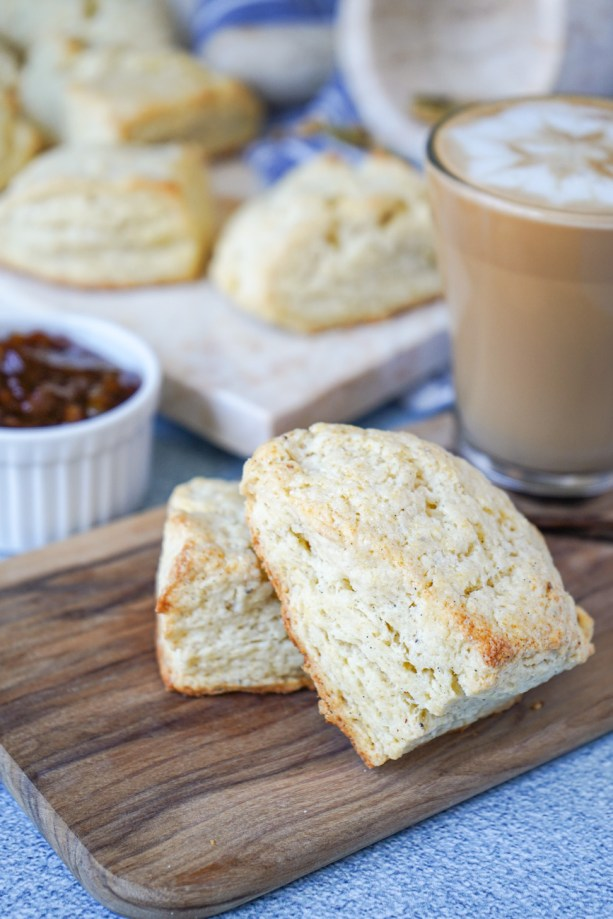 Side view of two Cardamom Vanilla Cream Scones on a wooden board next to a latte in a glass cup.