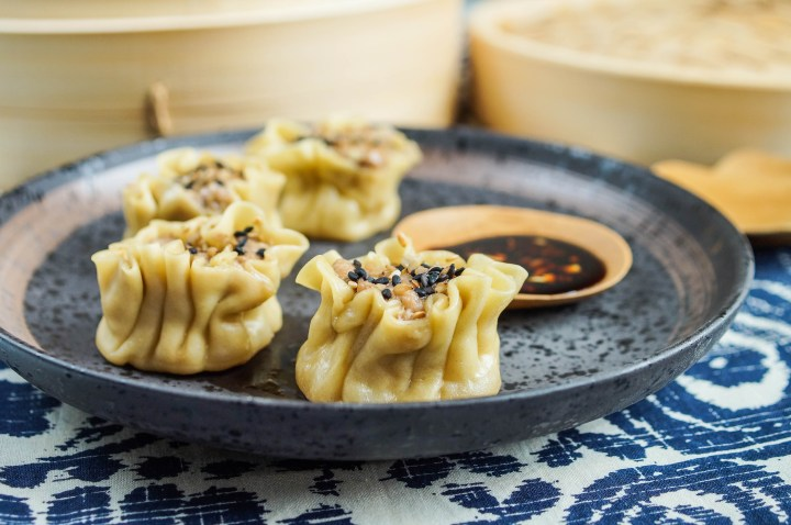 Four Shumai (Pork and Ginger Dumplings) on a brown plate with dipping sauce.