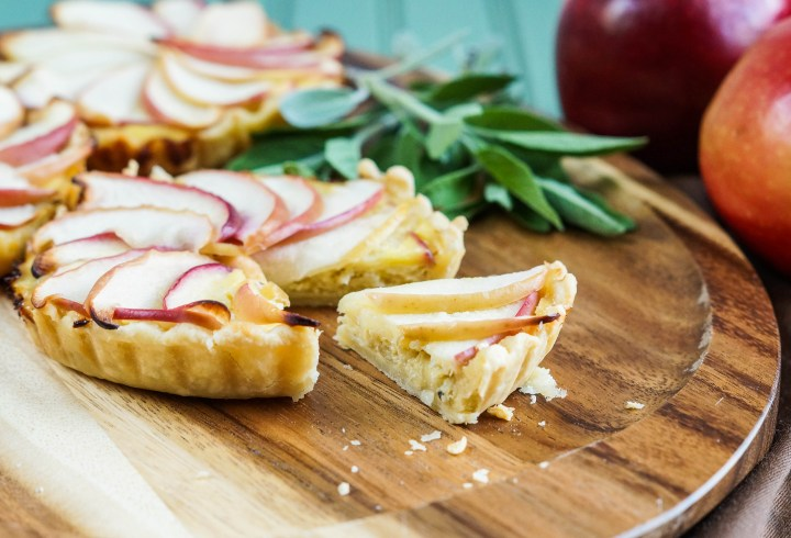 Three small Apple and Caramelized Onion Tarts on a wooden board with a small slice cut out.