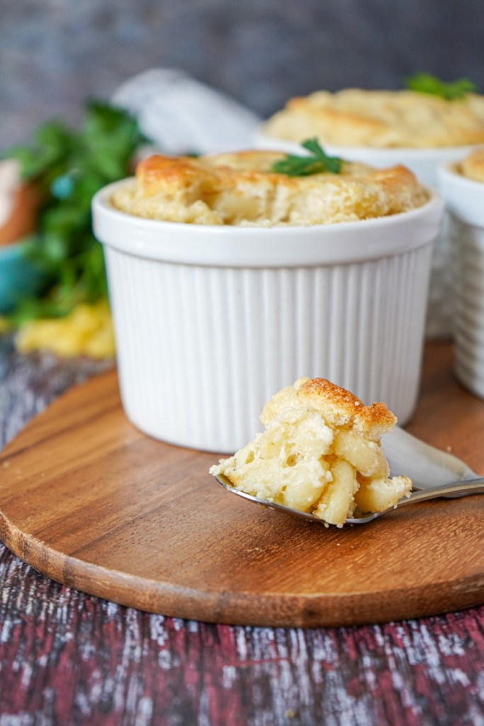 Spoonful of Macaroni and Cheese Soufflé in front of three white ramekins.
