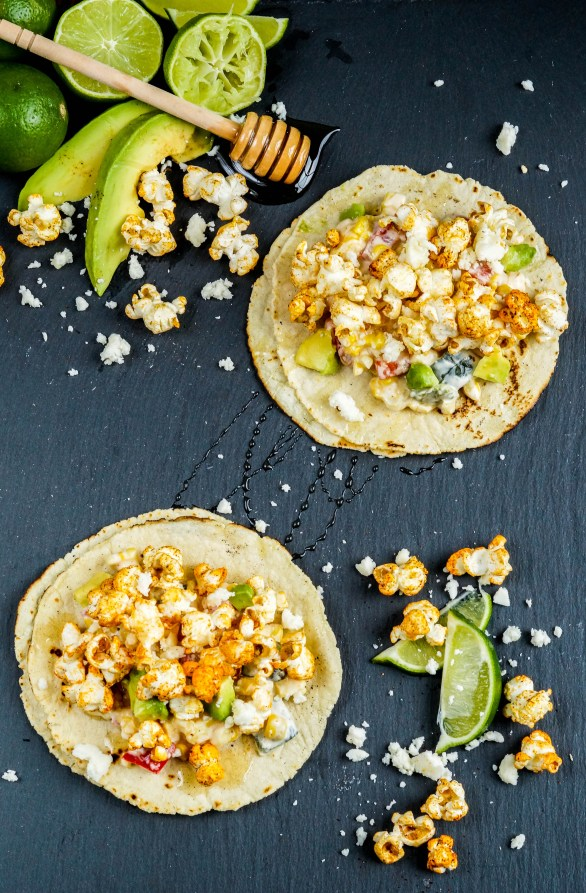 Aerial view of two Popcorn Tacos next to avocado slices, limes, and crumbled cheese.