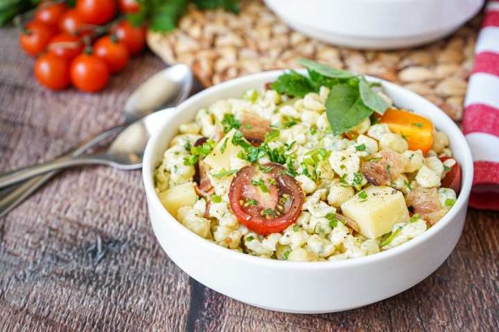 Spätzlesalat (German Spaetzle Pasta Salad) in a white bowl next to two spoons.