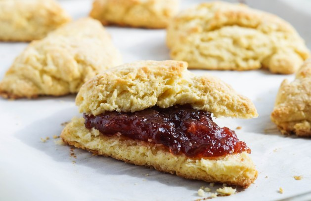 Sunny Scones on a parchment-lined baking sheet with the front one filled with jam.
