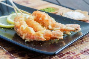 Three Jumbo Shrimp Tempura on a black plate.