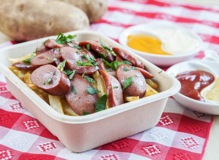Salchipapas (Peruvian Sausages and Potatoes) in a rectangular to-go container next to 2 russet potatoes and white dipping bowls filled with ketchup, mustard, aji Amarillo, and mayonnaise.