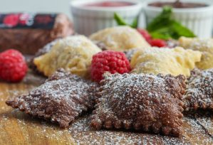 Plain and Chocolate Fried Ravioli with Raspberry Chocolate Goat Cheese on a wooden board