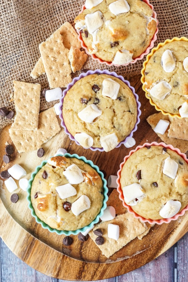 Aerial view of five S'mores Muffins on a wooden platter with scattered graham crackers, marshmallows, and chocolate chips.