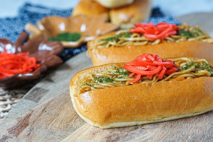 Yakisoba Pan- stir-fried noodles in a hotdog bun on a wooden platter