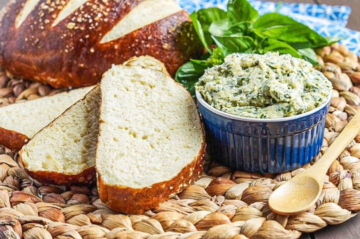 Kräuterbutter (German Herb Butter) in a small blue bowl next to slices of pretzel bread, a large bunch of basil, and a wooden spoon.