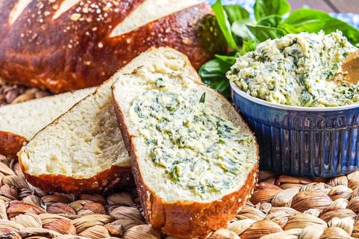 Kräuterbutter (German Herb Butter) in a small blue bowl and spread over a slice of pretzel bread.