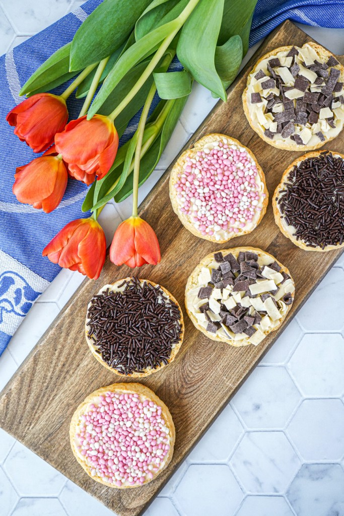 Aerial view of six Beschuit (Dutch Rusk) on a wooden board next to orange tulips.