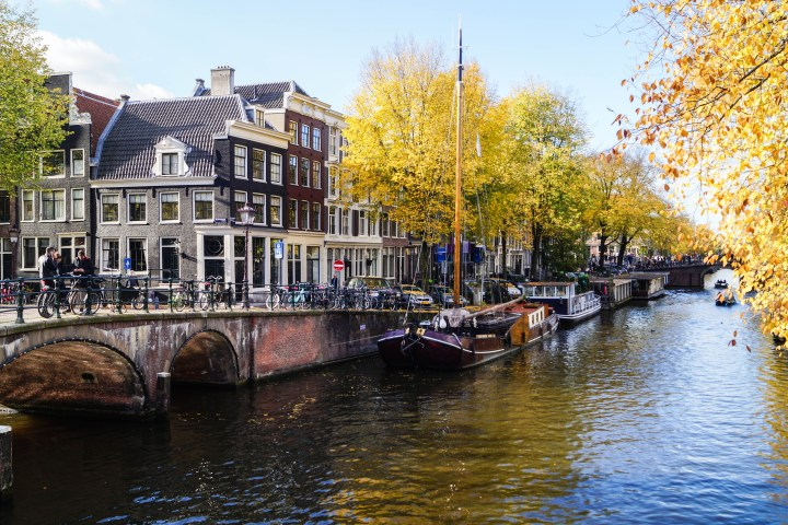 Canal in Amsterdam with a bridge, houseboats, and trees