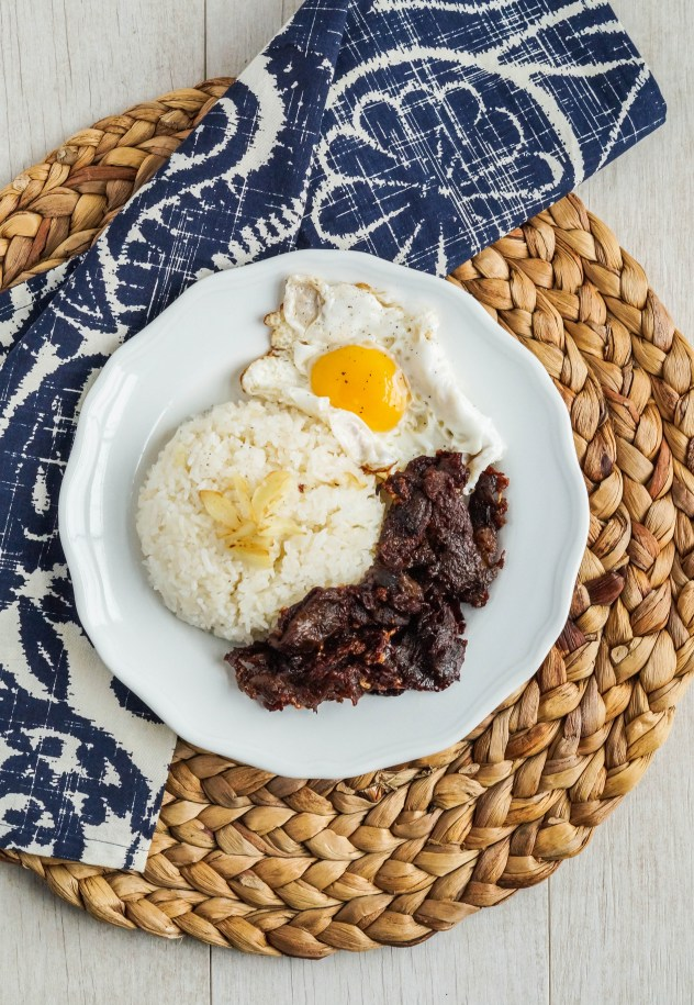 Aerial view of Tapa (Filipino Dried Cured Beef) on a white plate with garlic fried rice and a fried egg.