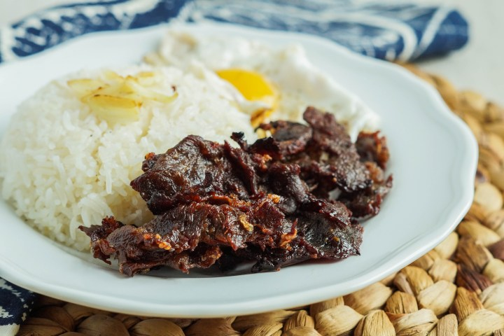Tapa (Filipino Dried Cured Beef) on a white plate with garlic fried rice and a fried egg.