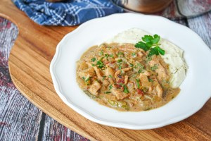 Kurzemes Strogonovs (Latvian Pork Stroganoff) on a white plate with mashed potatoes.