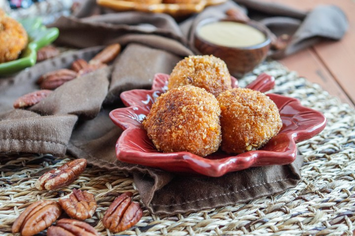 Three Sweet Potato Maple Pecan Goat Cheese Croquettes on a red plate next to a brown towel and a scattering of pecans.
