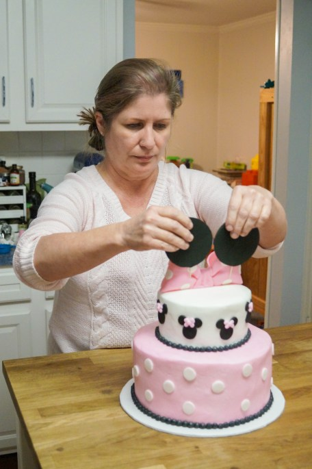 Placing Minnie Mouse ears on the top of the cake.