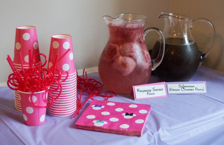 Two pitchers of punch next to Minnie Mouse paper cups and napkins.