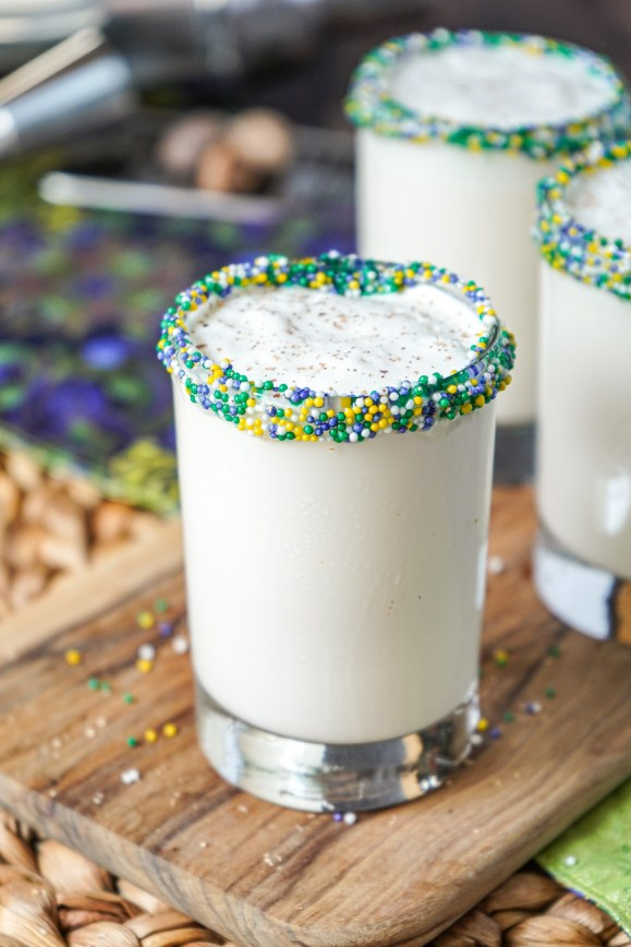 Close up of New Orleans Brandy Milk Punch in a clear glass with purple, green, and gold sprinkles around the rim.