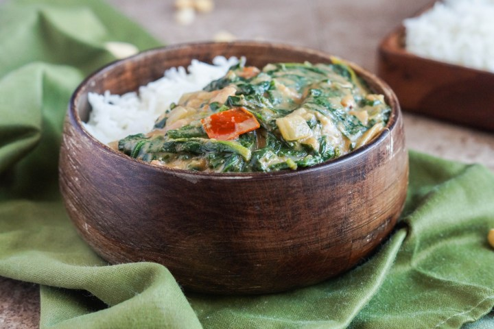 Close up of Gambian Spinach with Peanut Sauce in a wooden bowl with rice and resting on a green towel.