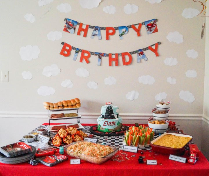 Red table covered in food, and cake, and a happy birthday banner on the wall.