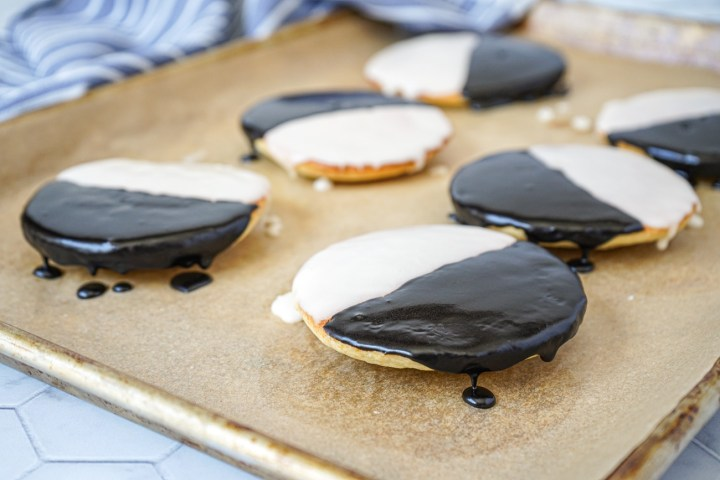 Side view of Black and White Cookies on a parchment-lined baking sheet.