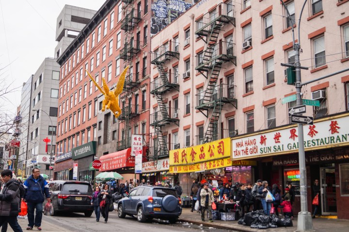Street in Chinatown with cars and vendors.