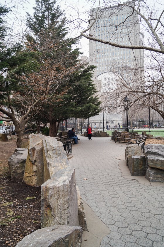 Walkway in Columbus Park with trees and a tall building in background.