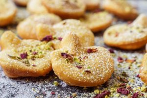 Afghani Gosh-e-Fil (Elephant Ear-Shaped Fried Pastry) topped with rose petals and crushed pistachios.