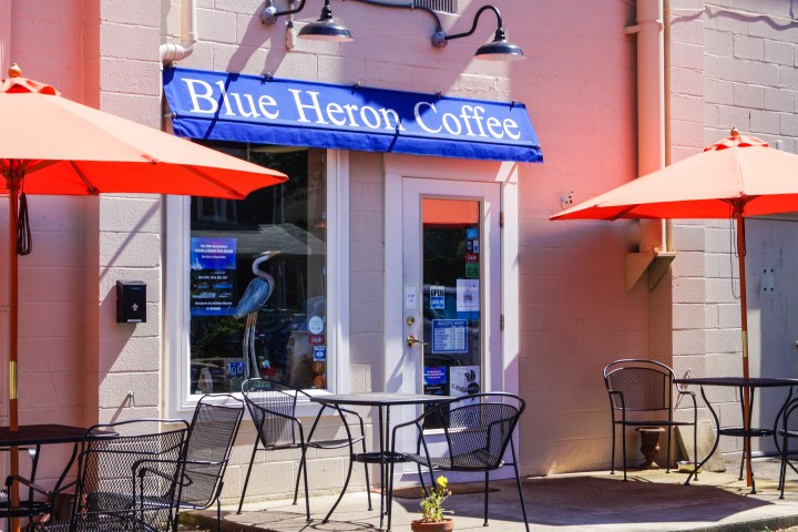 Outside of Blue Heron Coffee with black patio tables and orange umbrellas.
