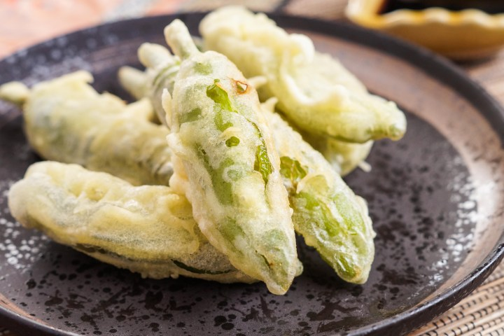 Shishito Tempura (Japanese Fried Shishito Peppers) arranged on a dark brown plate.