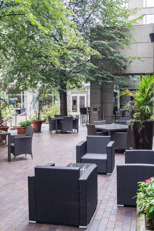 Courtyard at The Logan Hotel with armchairs situated around small tables.