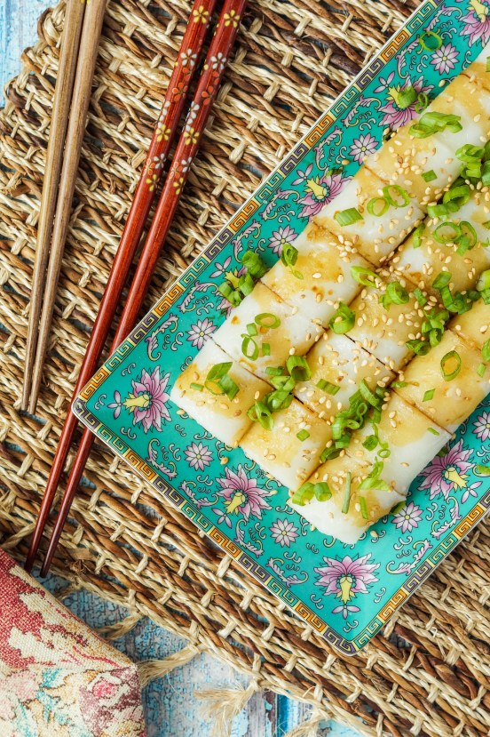 Aerial view of Cheung Fun (Steamed Rice Noodle Rolls) on a rectangular plate and topped with green onions and sesame seeds.