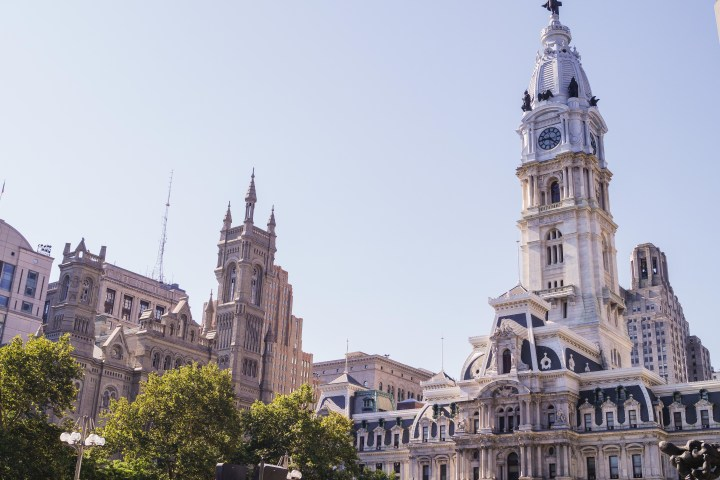 Outside of historical buildings in Philadelphia with a tall tower.
