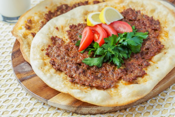 Lahmacun (Turkish Pizza) topped with tomatoes, parsley, and lemon