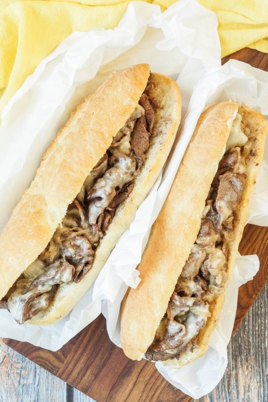 Aerial view of two Philly Cheesesteak on a white sheet of parchment next to a yellow towel.