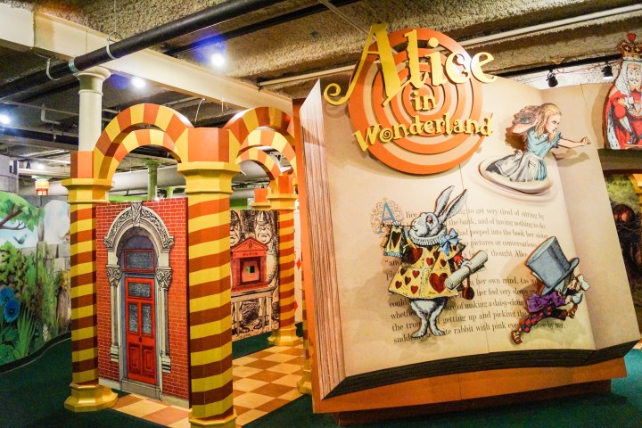 Entrance to Wonderland exhibit with a large Alice in Wonderland Book page.