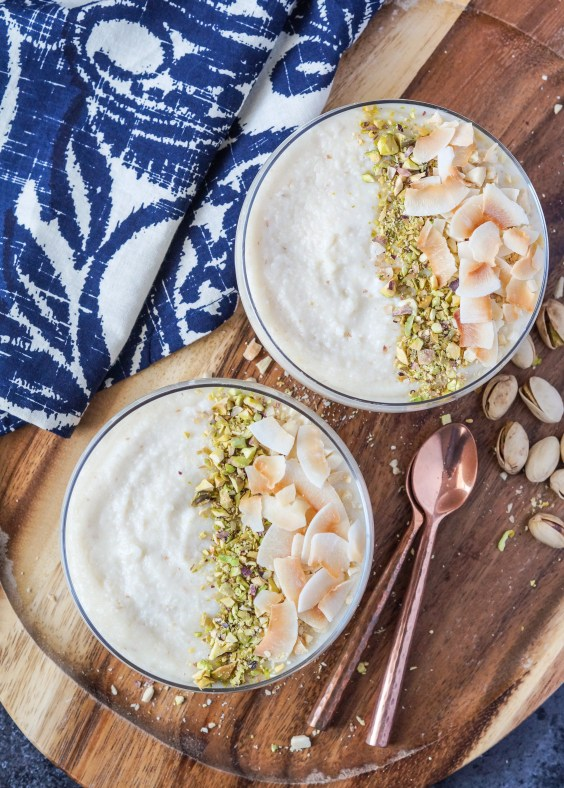 Aerial view of Keskul-e-Fugara (Turkish Milk and Almond Pudding) in two glasses topped with pistachios, almonds, and toasted coconut flakes. The glasses are resting on a wooden platter next to two copper spoons and scattered pistachios.