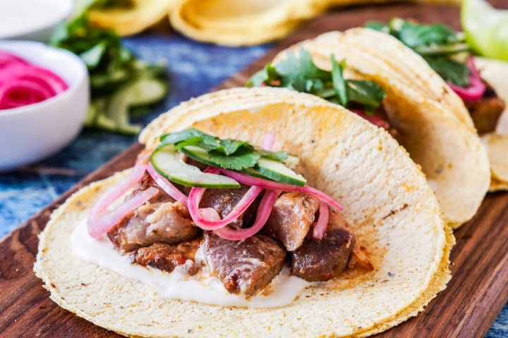 Close up of three Carnitas Tacos on a wooden board.