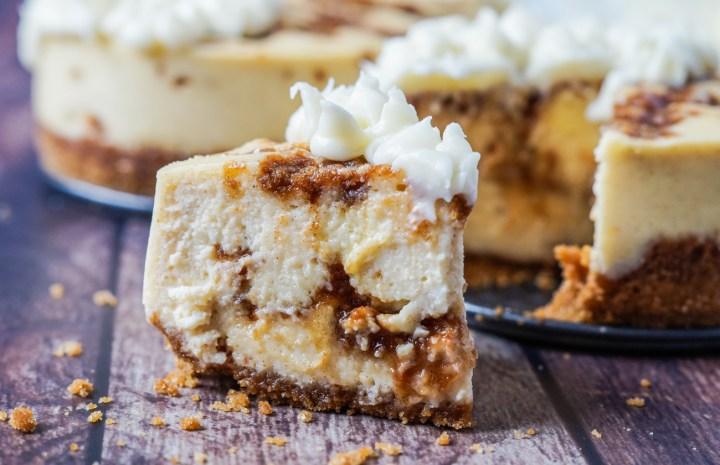 Slice of Cinnamon Roll Cheesecake in front of miniature cheesecakes.