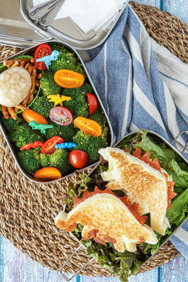Aerial view of Dinosaur Bento with two stegosaurus-shaped pepperoni and cheese sandwiches, broccoli, red and yellow cherry tomato halves, cracked soy sauce egg, and pretzel sticks in two parts of a silver bento box.