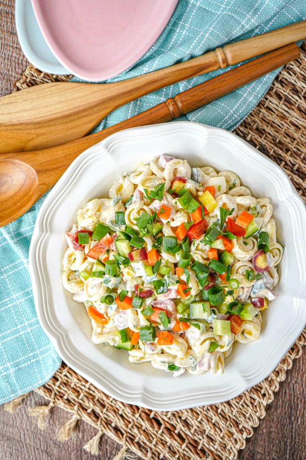 Aerial view of Springtime Pasta Salad in a white bowl next to two wooden spoons.