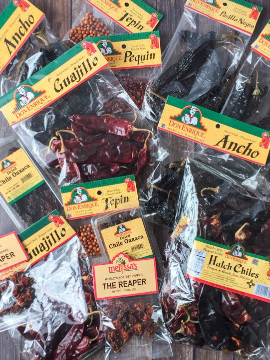 Aerial view of bags of different types of chiles- The Reaper, Ancho, Guajillo, Tepin, Pequin, and Hatch Chiles.