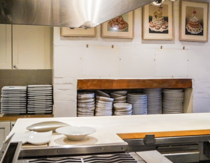 White plates and bowls stacked in the kitchen at the James Beard House.