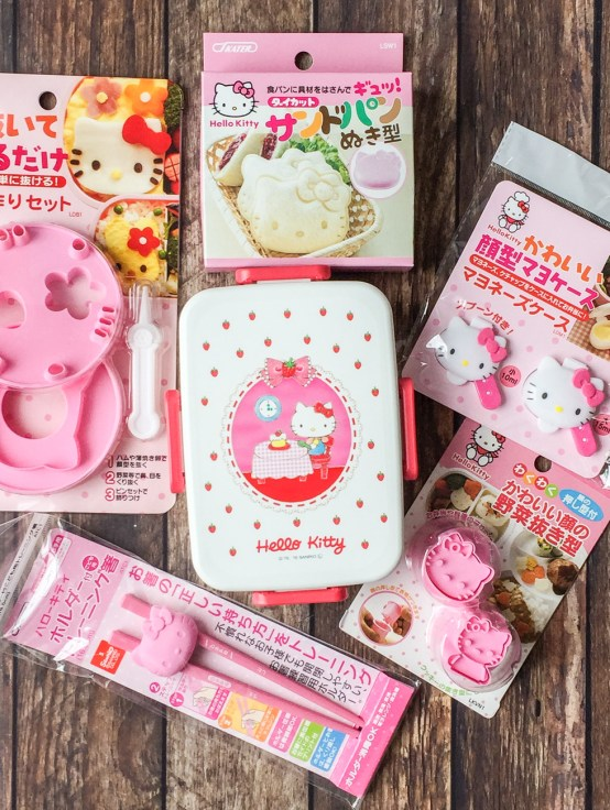 Aerial view of Hello Kitty Bento Supplies- bento box, cookie cutters, sandwich cutter, sauce holders, and chopsticks.