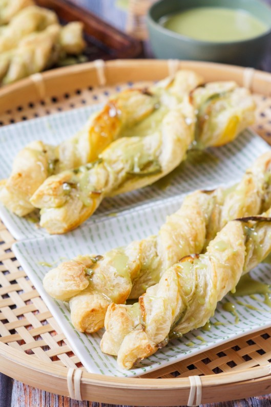 Four Matcha Puff Pastry Twists on two rectangular white plates with green dashes and a cup of green tea in the background.