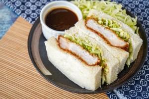 Two slices of Katsu Sando (Japanese Pork Cutlet Sandwich) on a dark brown plate with cabbage.