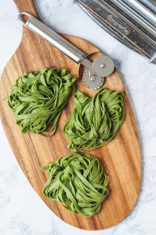 Homemade Spinach Fettuccine in bundles on a wooden platter next to a steel pastry cutter.