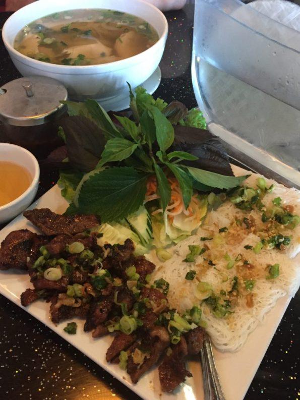 Bánh Hỏi Thịt Nướng ất Việt Chopsticks- rice noodles, herbs, and pork ơn a white square plate.
